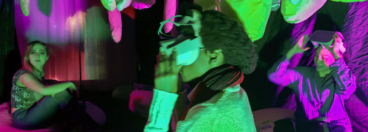 "People sitting at the multimedia art installation, ""Un-becoming Carbon,"" wear virtual reality goggles to see the vital relationship between plants and humans."
