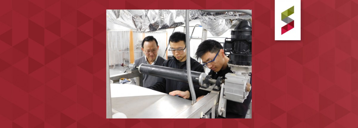 Winston Ho, graduate student Kai Chen, and Research Scientist Yang Han ('18 PhD) adjust the membrane substrate on Ho's membrane-manufacturing equipment in this photo from spring 2019.