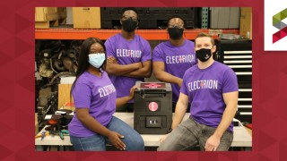 4 student members of Electrion team with battery pack
